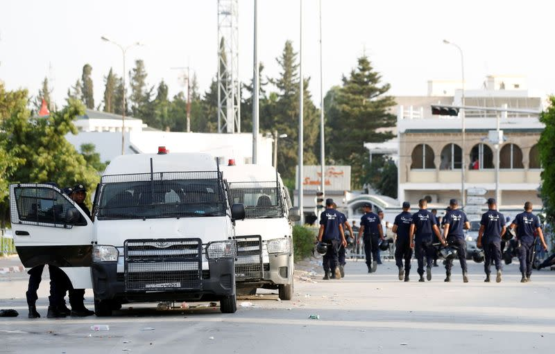 Police officers walk near the parliament building in Tunis