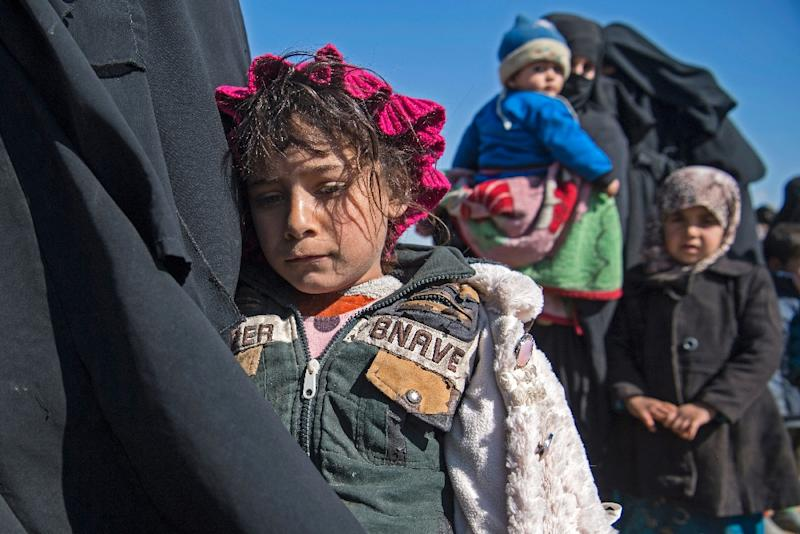 Women and children stand in a field after they fled from the Baghouz area in the eastern Syrian province of Deir Ezzor on February 12, 2019 during an operation by the US-backed Syrian Democratic Forces (SDF) to expel Islamic State group jihadists (AFP Photo/Fadel SENNA)