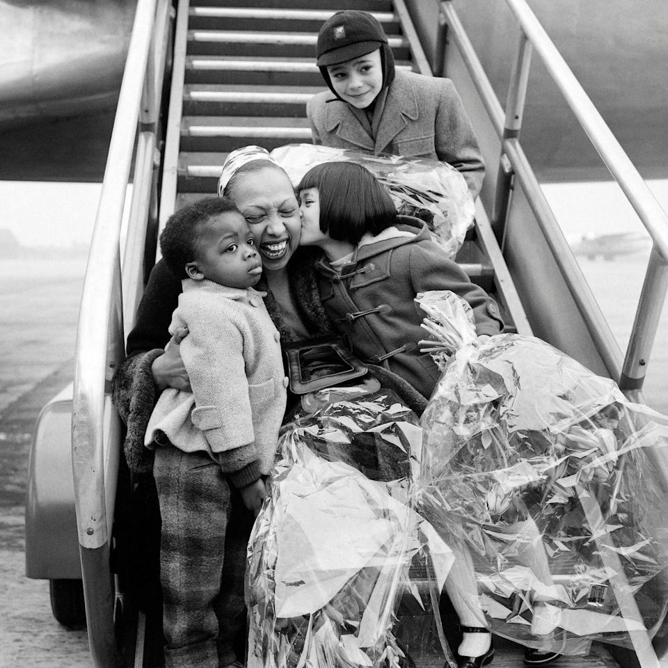"<p>After traveling for work, Josephine greets three of her adopted children at the airport in 1954. She and her husband, Jo Bouillon, adopted 12 children from various countries and ethnicities. Josephine <a href=""https://slate.com/culture/2014/04/josephine-bakers-rainbow-tribe-before-madonna-and-angelina-jolie-the-expat-dancer-adopted-12-children-from-around-the-globe.html"" rel=""nofollow noopener"" target=""_blank"" data-ylk=""slk:coined her family the &quot;Rainbow Tribe.&quot;"" class=""link rapid-noclick-resp"">coined her family the ""Rainbow Tribe.""</a></p>"