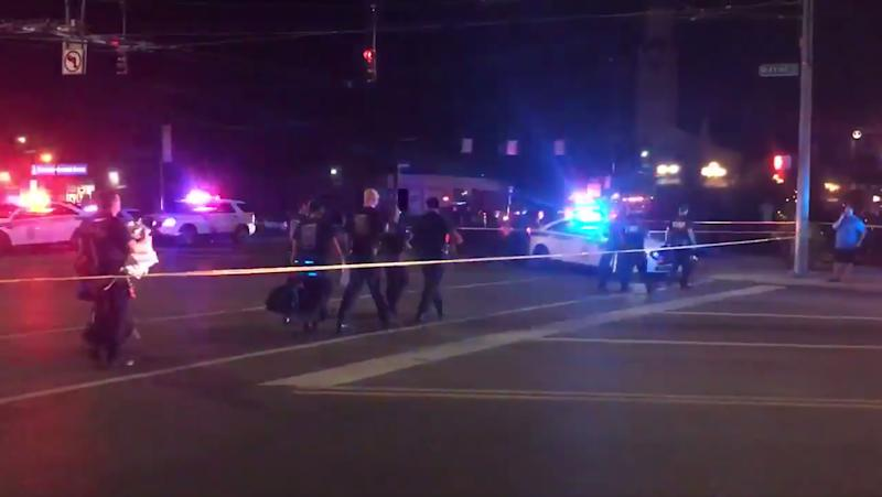 This videograb taken from the Twitter account of Derek Myers on August 4, 2019 shows police officers walking behind police cordon following a mass shooting in the popular bar and nightlife Oregon district in Dayton, Ohio. - Nine people were killed in a mass shooting early on August 4 in Dayton, Ohio, police said, adding that the assailant was shot dead by responding officers. (Photo by Derek MYERS / @DerekMyers Twitter account / AFP) (Photo credit should read DEREK MYERS/AFP/Getty Images)
