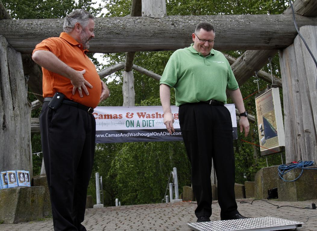 "Washougal Mayor Sean Guard, left, coaxes Camas Mayor Scott Higgins to step on the scales during their weigh-in in Washougal, Wash., Wednesday, May 2, 2012. The mayors of the two neighboring Washington state towns on the banks of the Columbia River are embarking on a ""Biggest Loser""style contest to see which of the two communities can lose the most weight in 12 months. (AP Photo/Don Ryan)"
