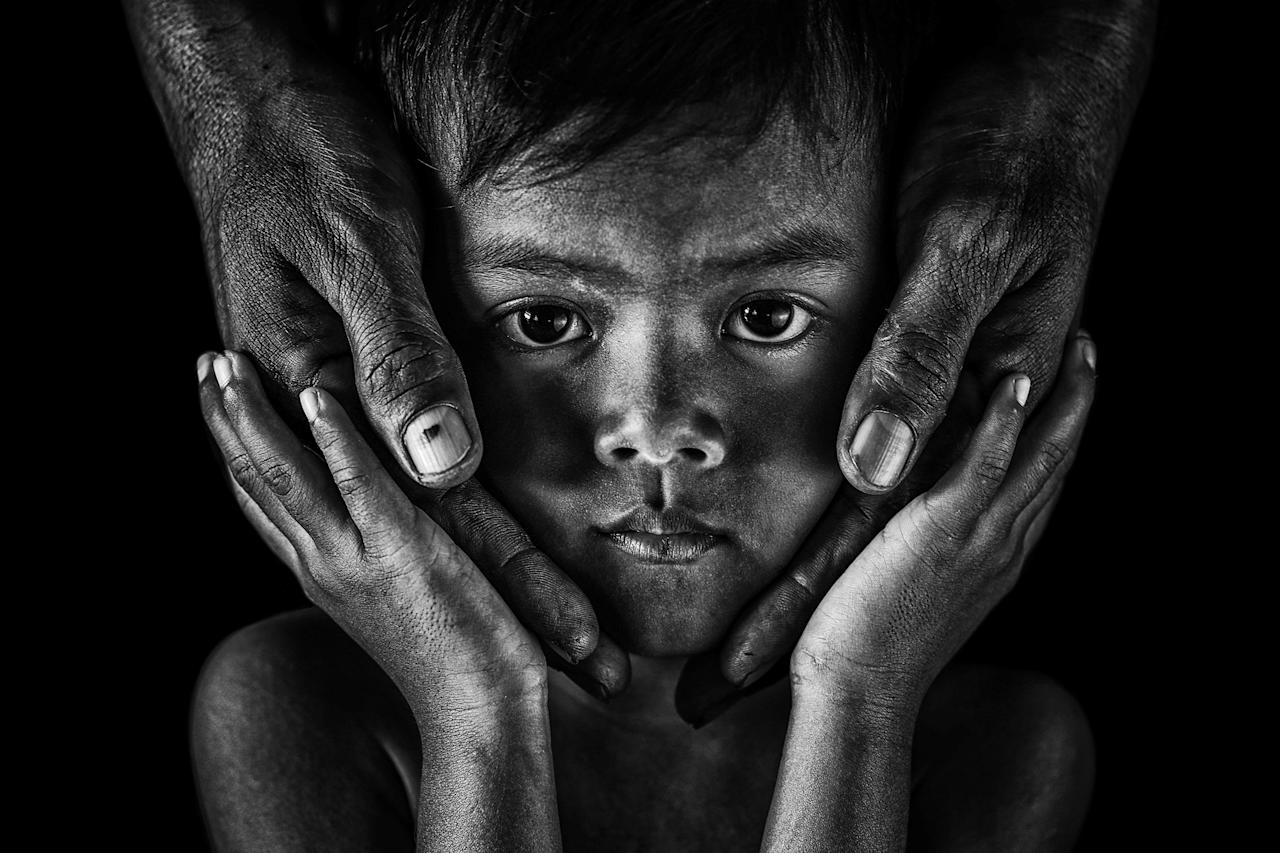 "<p>Portrait of a boy holding his father's hands on his face – Runner up was Andi Abdul Halil, 36, from Indonesia, who works as a ship's captain in Abu Dhabi, with his portrait of a boy holding his father's hands on his face. He said: ""I took the shot in my hometown Sungai Guntung, Riau, Indonesia. The idea was to capture a parent's love for his son. The hand is proof of how we give effort to our family.""<br />Source: Andi Abdul Halil / SWNS </p>"