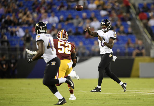 Baltimore Ravens quarterback Lamar Jackson, right, throws to running back Mark Thompson, left, over Washington Redskins linebacker Ryan Anderson (52) in the first half of a preseason NFL football game, Thursday, Aug. 30, 2018, in Baltimore. (AP Photo/Nick Wass)