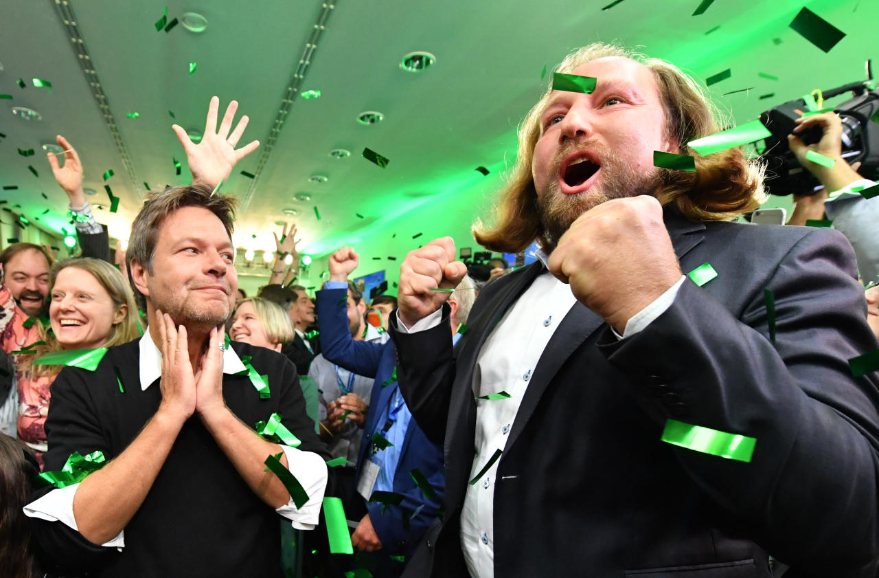 Party leaders Robert Habeck, left, and Anton Hofreiter, right, celebrate on the election party of the Green party in the state parliament in Munich, Germany, Sunday, Oct. 14, 2018, after the polling stations for the Bavarian state elections have closed. (AP Photo/Kerstin Joensson)