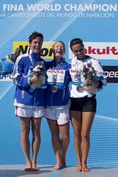 Silver medalist Ginger Huber from the U.S., left, gold medalist Cesilie Carlton from U.S., center, and bronze medalist Anna Bader from Germany, right, pose during the podium ceremony after the women's 20 meter high dive final at the FINA Swimming World Championships in Barcelona, Spain, Tuesday, July 30, 2013. (AP Photo/Daniel Ochoa de Olza)