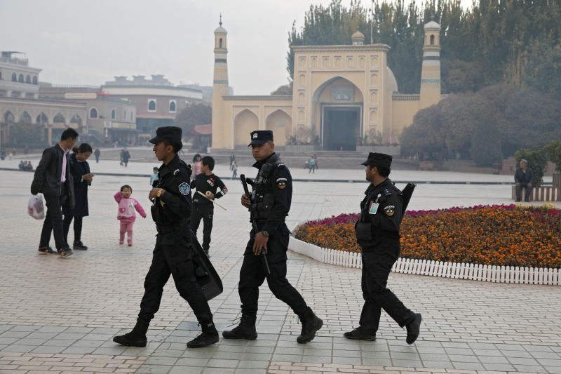 FILE - In this Nov. 4, 2017, file photo, Uighur security personnel patrol near the Id Kah Mosque in Kashgar in western China's Xinjiang region. A database obtained by The Associated Press offers the fullest and most personal view yet into how Chinese officials decided who to put into and let out of detention camps, as part of a massive crackdown that has locked away more than a million ethnic minorities, most of them Muslim. (AP Photo/Ng Han Guan, File)