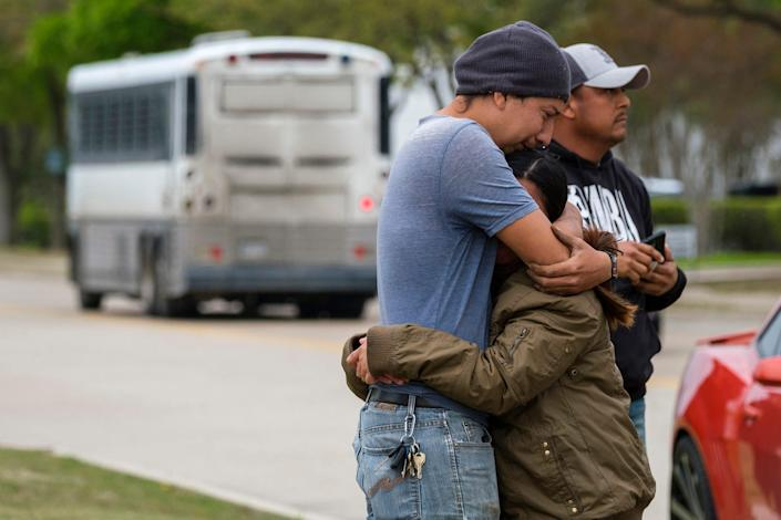 FILE - In this April 3, 2019, file photo, a couple who did not want to give their names embrace outside CVE Group as a bus from LaSalle Corrections Transport departs the facility in Allen, Texas. Immigrant families and advocates are warning about planned arrests around the country by the Immigration and Customs Enforcement agency.