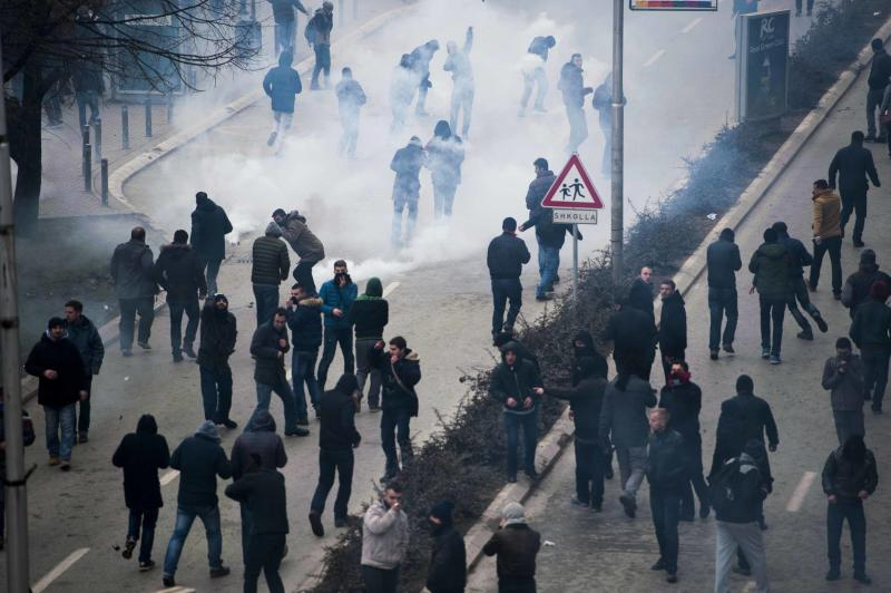 Some protestors run away from tear gas canisters thrown by riot police during clashes with protestors in Pristina, Kosovo on January 27, 2015 (AFP Photo/Armend Nimani)