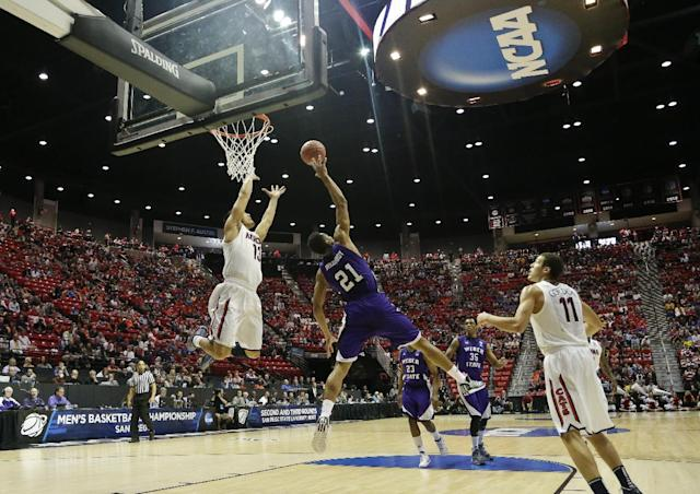Weber State forward Joel Bolomboy (21) gets up in the air to block a lob pass intended for Arizona guard Nick Johnson, left, during the first half in a second-round game in the NCAA college basketball tournament Friday, March 21, 2014, in San Diego. (AP Photo/Gregory Bull)