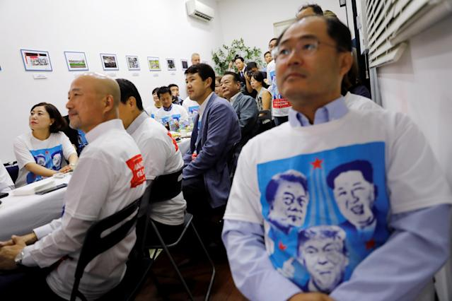 <p>At the Korean Association in Singapore, Koreans watch as President Trump meets North Korean leader Kim Jong Un on Tuesday. (Photo: Tyrone Siu/Reuters) </p>