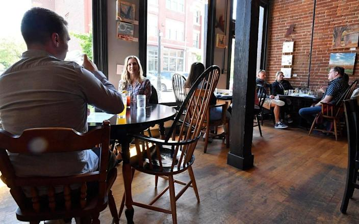 Happy about not being required to wear masks, Tucker Andis, left, and his mother, Liberty McLean, ate lunch Friday at The Farmhouse in the River Market. Kansas City Mayor Quinton Lucas announced Friday the city was fully lifting its emergency order.