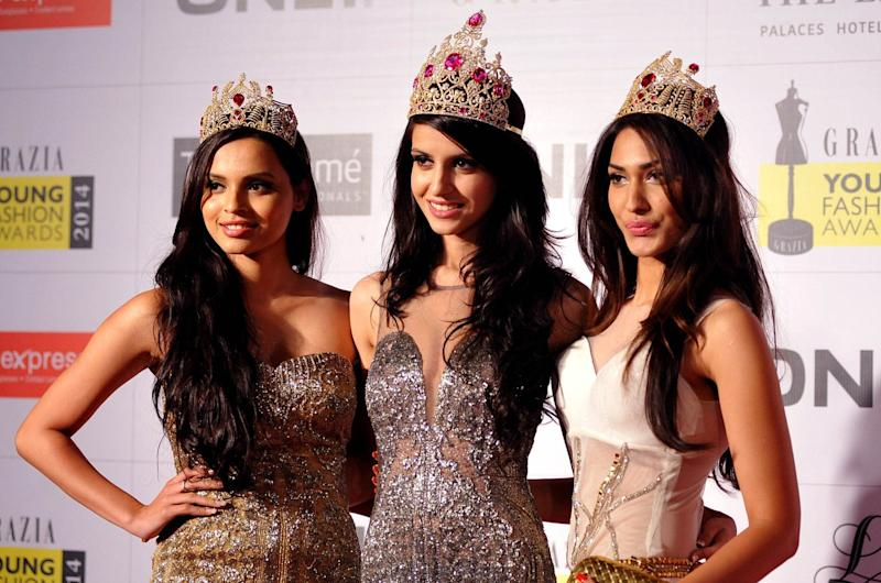 Indian Femina Miss India World 2014 Koyal Rana (L), Femina Miss India Earth 2014 Jhataleka Malhotra (C) and Femina Miss India Supernational 2014 Gail Nicole Da Silva pose for a photograph during the Grazia Young Fashion Awards 2014 ceremony in Mumbai on late April 13, 2014. AFP PHOTO/STR (Photo credit should read STRDEL/AFP/Getty Images)