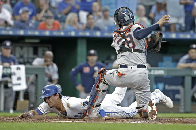 Kansas City Royals' Nicky Lopez scores against Houston Astros catcher Robinson Chirinos on a double by Whit Merrifield during the third inning of a baseball game Saturday, Sept. 14, 2019, in Kansas City, Mo. Lopez was originally called out, but the ruling was changed after review. (AP Photo/Charlie Riedel)