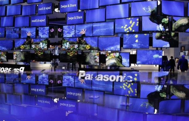 People pass a television installation at the Panasonic pavilion before the start of the IFA consumer electronics fair in Berlin, August 29, 2012.