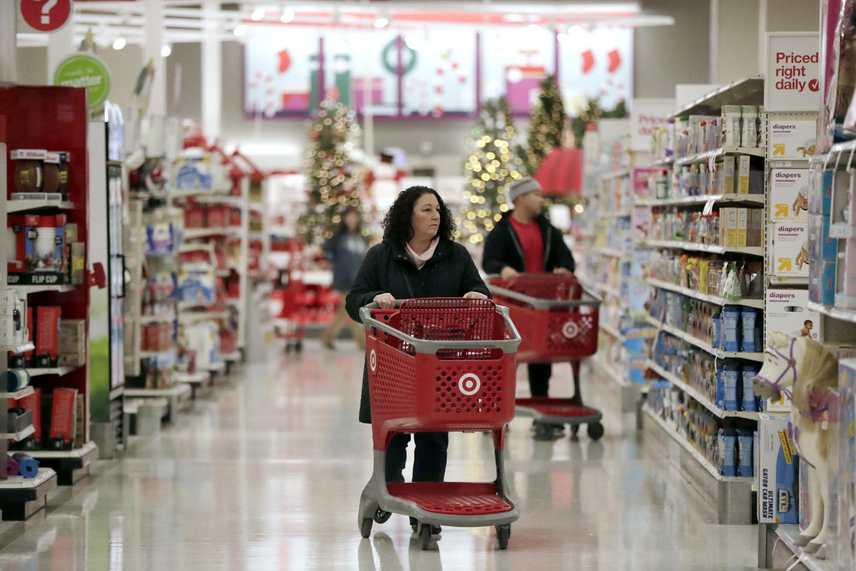 In this Friday, Nov. 16, 2018, photo, shoppers push carts while browsing isles at a Target store in Edison, N.J. Shoppers are spending freely heading into the holidays, but heavy investments and incentives like free shipping by retailers are giving Wall Street pause. Target Inc., Kohl's Corp., Best Buy Co. and TJX Cos. all reported strong sales at stores opened at least a year. (AP Photo/Julio Cortez)