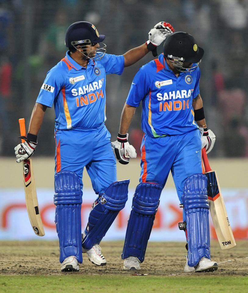 Indian batsman Suresh Raina (R) congratulates his teammate Virat Kholi (L) as he leaves the field after his dismissal during the one day international (ODI) Asia Cup cricket match between India and Pakistan at The Sher-e-Bangla National Cricket Stadium in Dhaka on March 18, 2012. AFP PHOTO/Munir uz ZAMAN (Photo credit should read MUNIR UZ ZAMAN/AFP/Getty Images)
