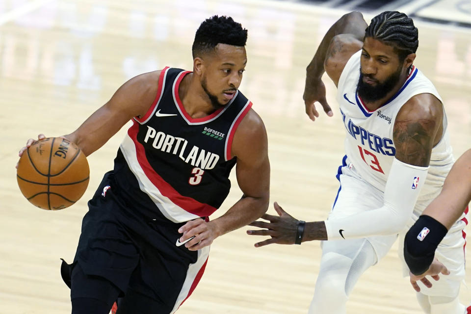 Portland Trail Blazers guard CJ McCollum (3) dribbles past Los Angeles Clippers guard Paul George (13) during the first half of an NBA basketball game Tuesday, April 6, 2021, in Los Angeles. (AP Photo/Marcio Jose Sanchez)
