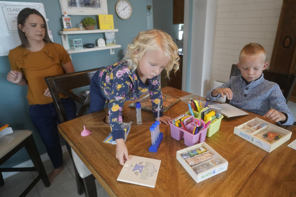 Stefanie Plothow home schools her children Cameron, 9, in the 3rd grade, and Ainsley, 5, in kindergarten, Friday, Aug. 20, 2021, in Lehi, Utah. A group of Utah parents is suing the state over a law that bans school districts from approving mask mandates. It's the latest U.S. legal challenge over rules for face coverings in the classroom. (AP Photo/Rick Bowmer)
