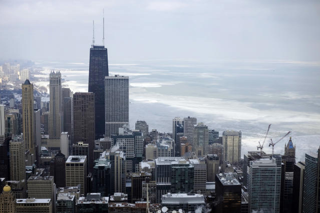 FILE - In this Feb. 17, 2015, file photo, ice covered Lake Michigan is seen behind downtown skyline, in Chicago. Big cities, like Chicago, aren't growing like they used to. New figures released by the U.S. Census Bureau on Thursday, May 23, 2019, show most of the nation's largest cities last year grew by a fraction of the numbers they did earlier this decade. (AP Photo/Kiichiro Sato, File)