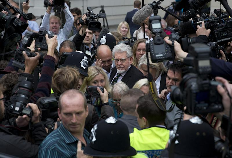 Veteran entertainer Rolf Harris, center, leaves Westminster Magistrate's Court in London, Monday, Sept. 23, 2013. Harris faces nine counts of indecent assault on victims aged 14 and 15 and four counts of making indecent images. Harris, 83, has had musical hits, hosted television shows, painted an official portrait of the queen for her 80th birthday in 2006, and performed at the monarch's Diamond Jubilee concert last year. (AP Photo/Matt Dunham)