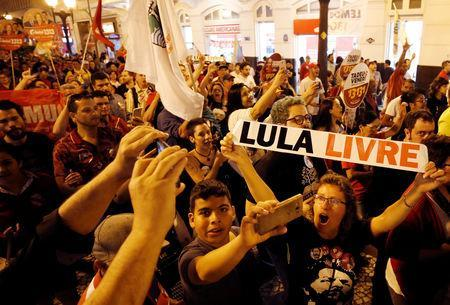 """FILE PHOTO: Supporters of the former Brazilian President Luiz Inacio Lula da Silva attend a rally in Curitiba, Brazil August 30, 2018. Picture taken August 30, 2018. The sign reads """"Free Lula."""" REUTERS/Rodolfo Buhrer"""