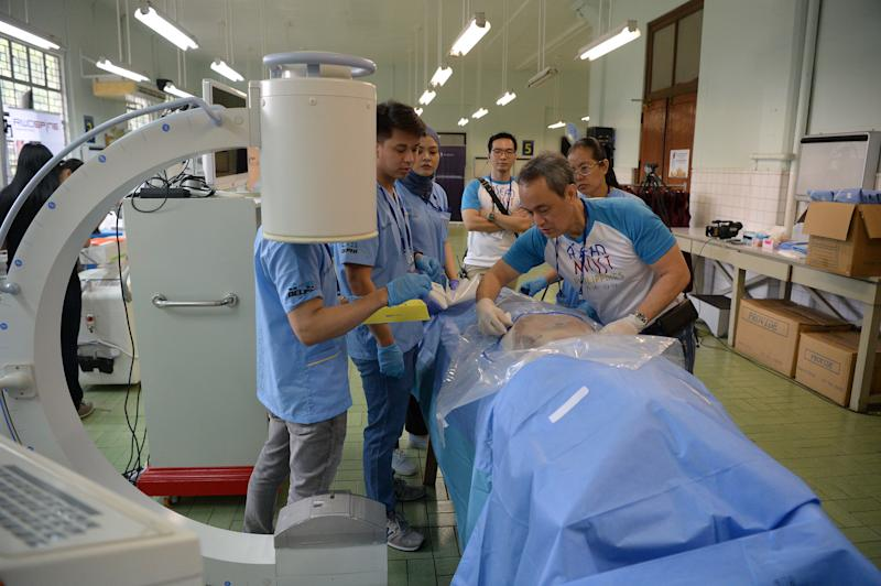 File Photo: Filipino doctor Rafael Bundoc (front R) from the University of the Philippines medical school, along with nurses, prepares one of the cadavers for a spine surgery workshop at the anatomy room of the university in Manila on June 26, 2019. (Photo: TED ALJIBE/AFP via Getty Images)