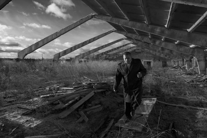 In this Nov. 14, 2012, photo, Eduard Mochalov, editor of The Bribe, walks through a derelict hog barn on his abandoned farm in Yarabaikasy near Cheboksary, the capital city of Chuvashia, Russia. Mochalov has found a new lease on life as a crusading journalist investigating corruption in his native region, fueled by tips from disgruntled businessmen and government workers. Undeterred by a system where the law is selectively used to protect the powerful and crack down on critics, Mochalov has quickly earned cult status _ not to mention the ire of countless local officials _ throughout the small province of Chuvashia. (AP Photo/Alexander Zemlianichenko)