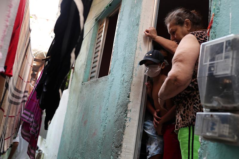 A woman and a child wearing a facemask stand in the doorway of their home in the city's biggest slum Paraisopolis after residents have hired a round-the-clock private medical service to fight the coronavirus disease (COVID-19), in Sao Paulo, Brazil March 30, 2020. Picture taken March 30, 2020. REUTERS/Amanda Perobelli