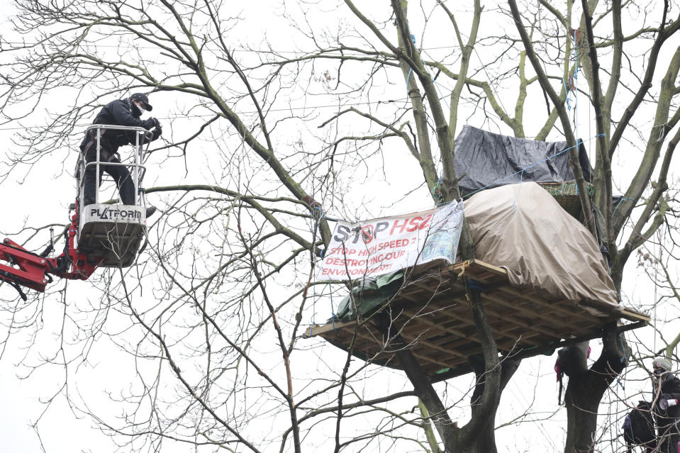 A cherry picker approaches an HS2 Rebellion treetop camp in an encampment in Euston Square Gardens in central London,, Wednesday Jan. 27, 2021. Protesters against a high-speed rail link between London and the north of England said Wednesday that some of them have been evicted from a park in the capital after they dug tunnels and set up a makeshift camp. (Aaron Chown/PA via AP)