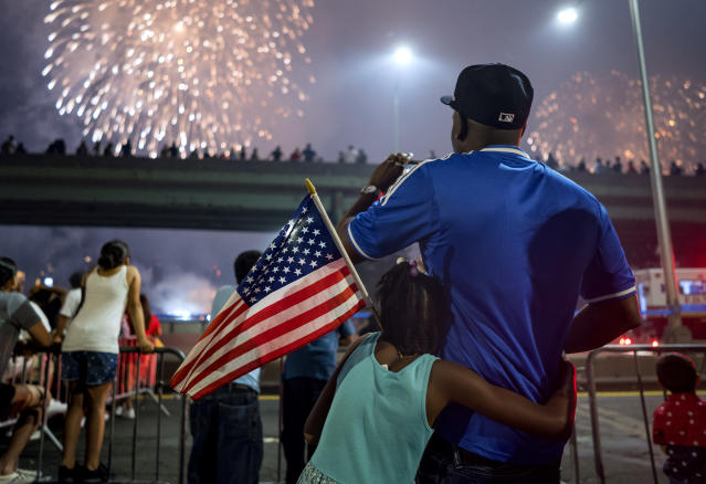 <p>Deon Stewart and his daughter Semiyah, of New York, join other spectators as they watch a fireworks display on the east side of Manhattan, part of Independence Day festivities Wednesday, July 4, 2018, in New York. (Photo: Craig Ruttle/AP) </p>