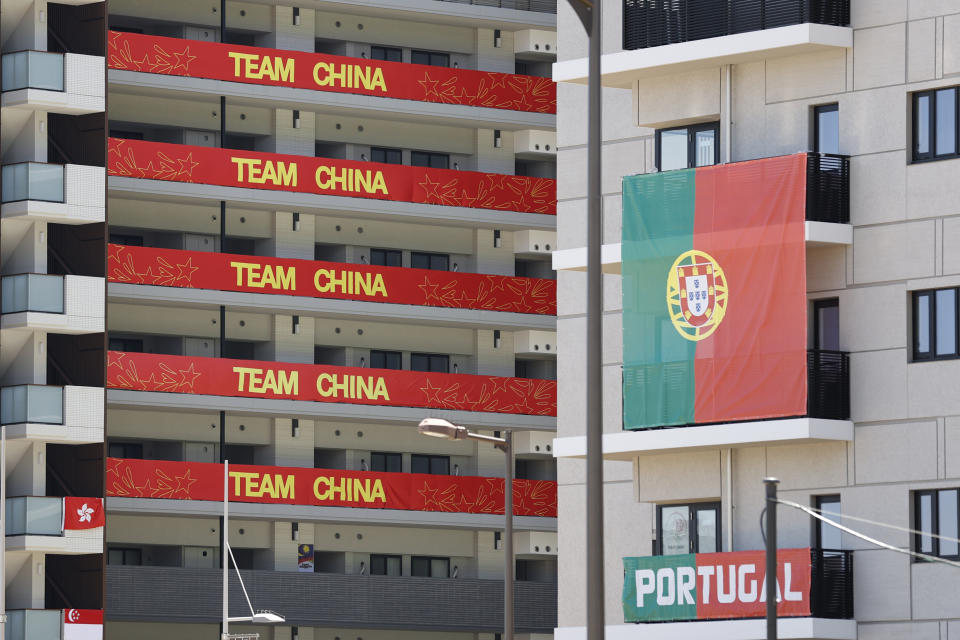 Flags of Team China and Portugal hanging on residential buildings in the athletes' village for the Tokyo Olympics.