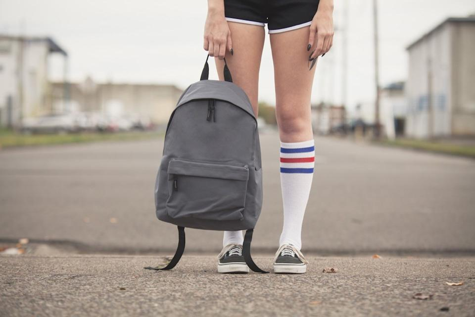 Girl holding generic backpack wearing black shorts and tube sock with tennis shoes standing on vacant street lies kids tell their parents