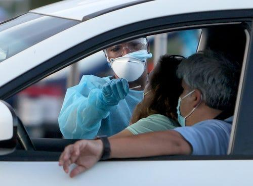 A healthcare worker at a 24-hour drive-thru site set up by Miami-Dade and Nomi Health in Tropical Park administers a COVID-19 test on August 30, 2021 in Miami, Florida.