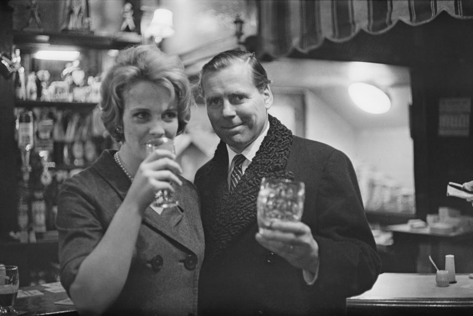 Irish producer and screenwriter Kevin McClory (1924-2006) pictured with his wife Frederica Sigrist having a celebratory drink in a pub bar on 3rd December 1963. McClory is celebrating after winning his High Court case against Ian Fleming over rights to the James Bond screenplay 'Thunderball'. (Photo by Harold Clements/Daily Express/Hulton Archive/Getty Images)