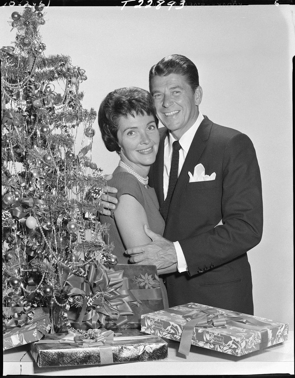 <p>Long before his political career, Reagan and his wife give each other a warm embrace as they celebrate the holiday season in 1961. He kept things simple with a suit, tie, and white pocket square.</p>