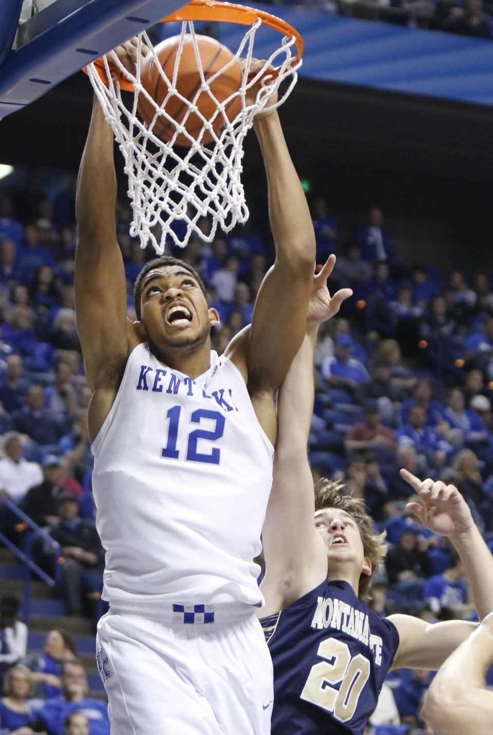 Kentucky's Karl-Anthony Towns (12) dunks next to Montana State's Ryan Shannon during the second half of an NCAA college basketball game, Sunday, Nov. 23, 2014, in Lexington, Ky. Kentucky won 86-28. (AP Photo/James Crisp)