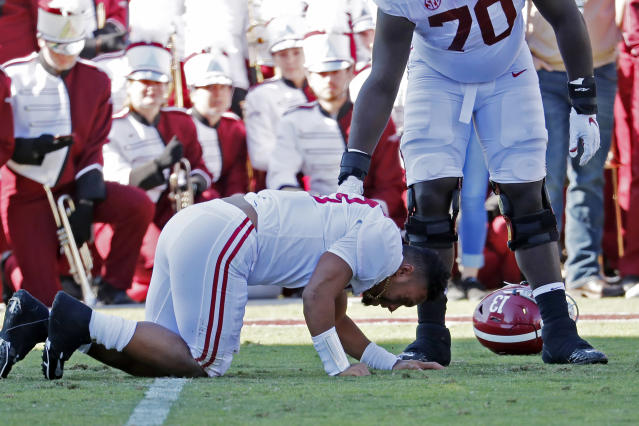 Alabama lineman Alex Leatherwood (70) checks on quarterback Tua Tagovailoa (13) after he was injured in the first half on Saturday. (AP)