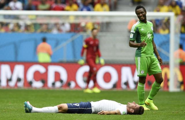 Nigeria's John Obi Mikel (R) reacts after fouling France's Olivier Giroud during their 2014 World Cup round of 16 game at the Brasilia national stadium in Brasilia June 30, 2014. REUTERS/Dylan Martinez (BRAZIL - Tags: SOCCER SPORT WORLD CUP)