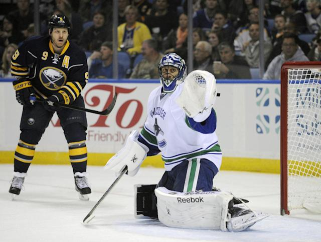 Buffalo Sabres' Steve Ott (9) and Vancouver Canucks' Roberto Luongo (1) watch a shot miss the net during the first period of an NHL hockey game in Buffalo, N.Y., Thursday, Oct. 17, 2013. (AP Photo/Gary Wiepert)