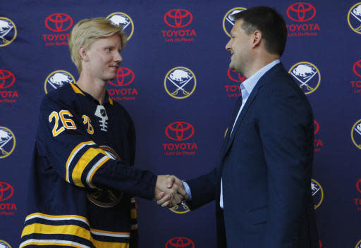 FILE - In this June 25, 2018, file photo, Rasmus Dahlin, of Sweden, left, the Buffalo Sabres No. 1 pick at the NHL draft on Friday, shakes hands with Sabres general manager Jason Botterill during an NHL hockey news conference, in Buffalo N.Y. The Buffalo Sabres have signed Dahlin to a three-year, entry-level contract. The signing was announced by the team Monday, July 9, 2018. (AP Photo/Jeffrey T. Barnes, File)