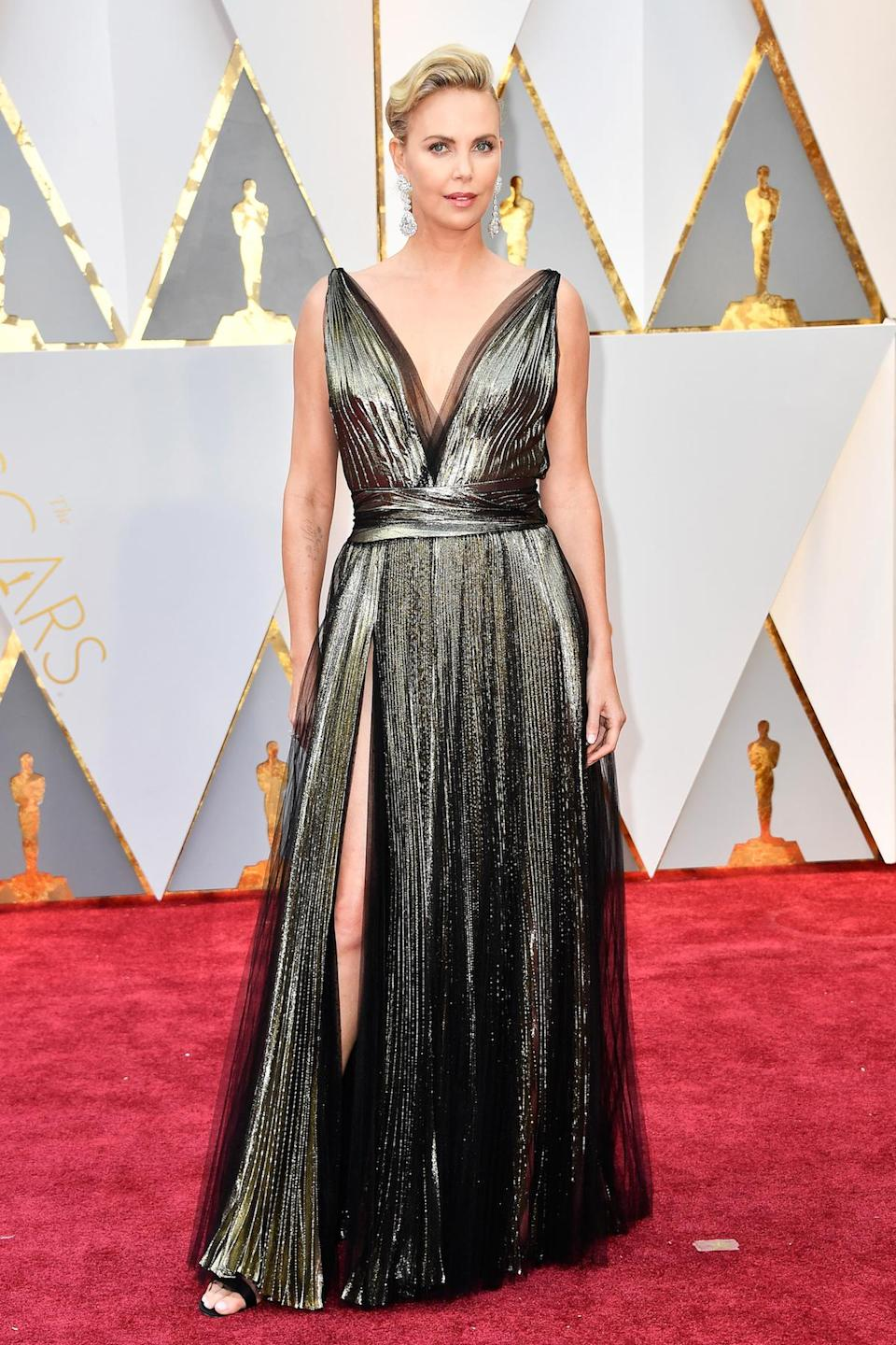 <p>Charlize Theron consistently delivers an amazing look on just about any red carpet she steps out on. Wearing a metallic Dior gown with a thigh-high slit and low-cut neckline, she did so yet again. <em>(Photo: Getty Images)</em> </p>