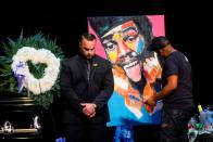 An artist paints a portrait for late rapper Marcel Theo Hall, known by his stage name Biz Markie, next to his casket during the funeral service in Patchogue