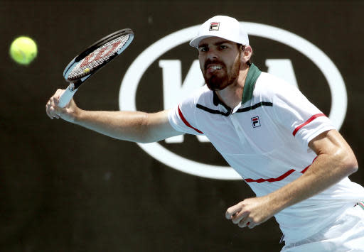 Reilly Opelka of the U.S. makes a forehand return to Italy's Fabio Fognini during their first round singles match at the Australian Open tennis championship in Melbourne, Australia, Tuesday, Jan. 21, 2020. (AP Photo/Dita Alangkara)