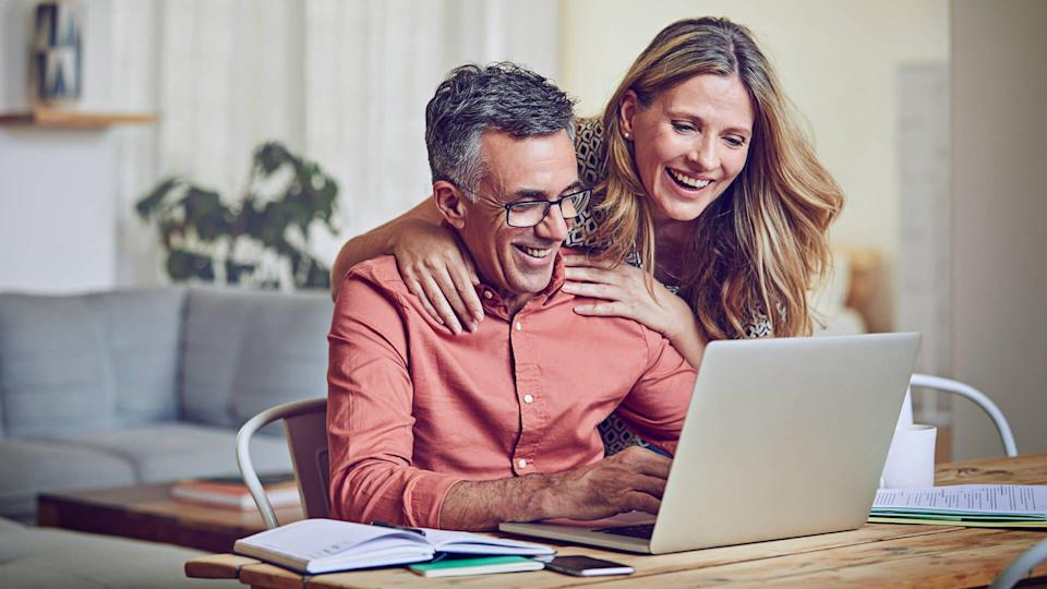 Shot of a mature woman leaning on her husband while he works on his laptop.