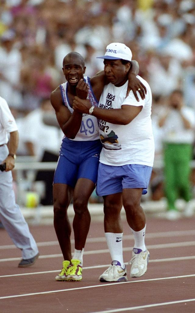 Aug 1992: Derek Redmond of Great Britain is helped towards the finish line by his father Jim Redmond after suffering an injury in the 400m semi-final at the Barcelona Olympic Games in Spain. \ Mandatory Credit: Gray Mortimore /Allsport