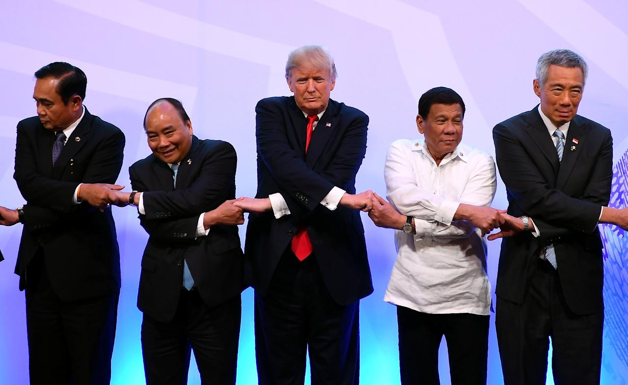 Thailand's Prime Minister Prayut Chan-o-Cha, Vietnam's Prime Minister Nguyen Xuan Phuc, U.S. President Donald Trump, Philippine's President Rodrigo Duterte and Singapore's Prime Minister Lee Hsien Loong pose for a family photo during the ASEAN-US 40th Anniversary commemorative Summit in Manila, Philippines November 13, 2017. REUTERS/Manan Vatsyayana/Pool