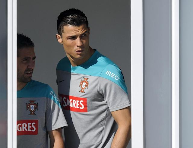 Cristiano Ronaldo and Joao Moutinho, left, peek from the dressing room prior to a training session of Portugal in Campinas, Brazil, Friday, June 20, 2014. Portugal plays in group G of the Brazil 2014 soccer World Cup. (AP Photo/Paulo Duarte)