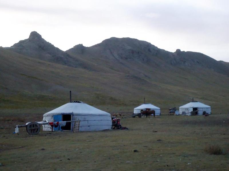 In this Sept. 10, 2011 photo, the sun sets behind a small cluster of nomadic tents, called gers, on the shore of Terkhiin Tsagaan Nuur, also known as White Lake, in central Mongolia. Yak carts, the main mode of transportation for these families, are parked outside each ger. (AP Photo/Louise Chu)