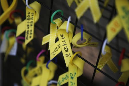 Yellow ribbons dedicated to the victims of the Sewol ferry disaster are seen hung on a fence in central Seoul November 11, 2014. REUTERS/Kim Hong-Ji