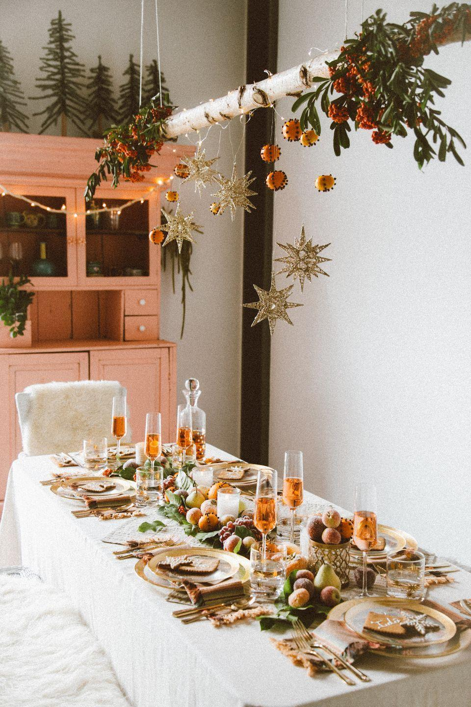 "<p>Take your Christmas centerpiece to new ""heights"" by hanging some ornaments and pendants above your dining room table. The result? A setup with floor-to-ceiling appeal.</p><p><a href=""https://blog.jungalow.com/2015/11/a-boho-ho-holiday-party-with-pier-1.html"" rel=""nofollow noopener"" target=""_blank"" data-ylk=""slk:Via the Jungalow"" class=""link rapid-noclick-resp""><em>Via the Jungalow</em></a></p>"